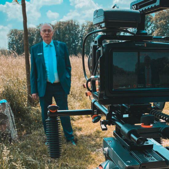 Paul Löneke steht im Hintergrund auf einer Wiese, im Vordergrund steht eine Filmkamera